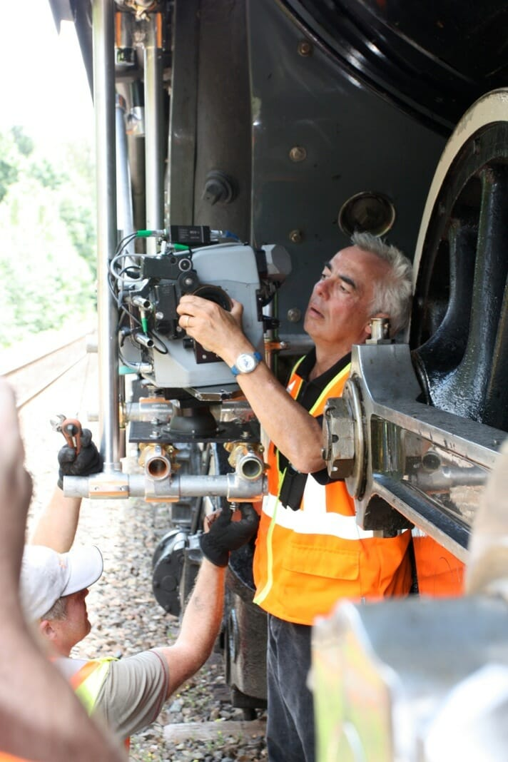 Filmmaker Stephen Low makes adjustments to the camera in preparation for shooting a sequence from behind the driving wheels of the locomotive.