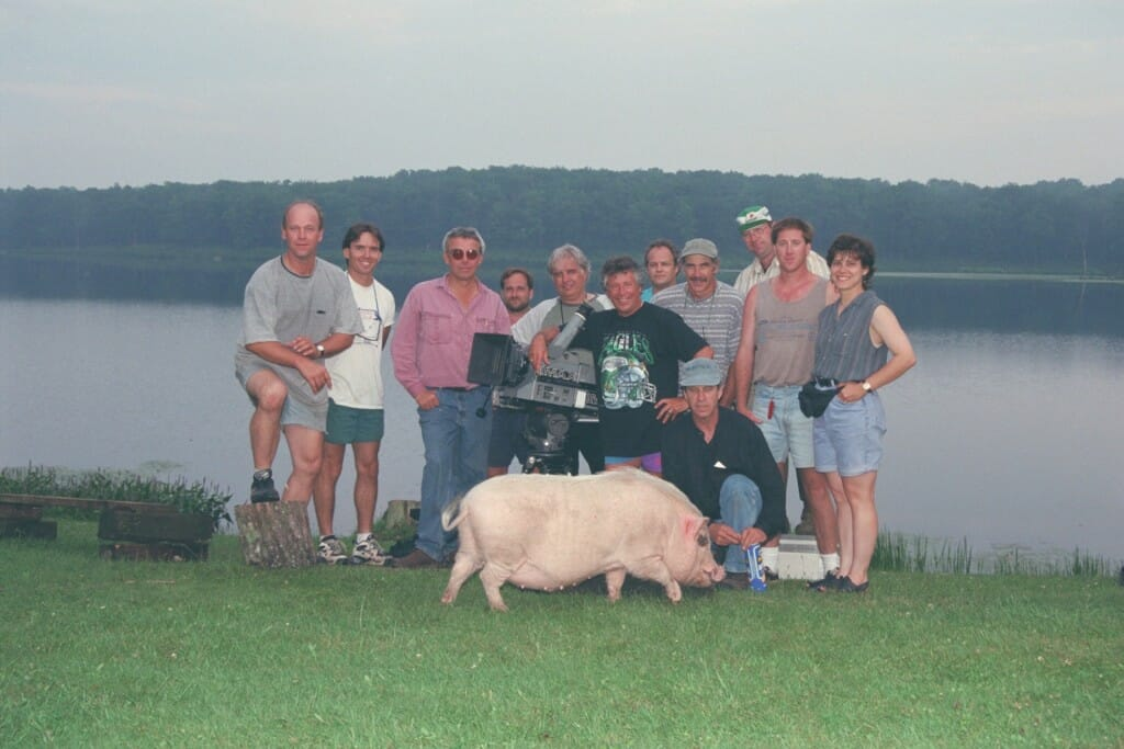 The crew of Super Speedway take a break during filming with Mario Andretti and his pet pig. Photo: Patrick Gariup.