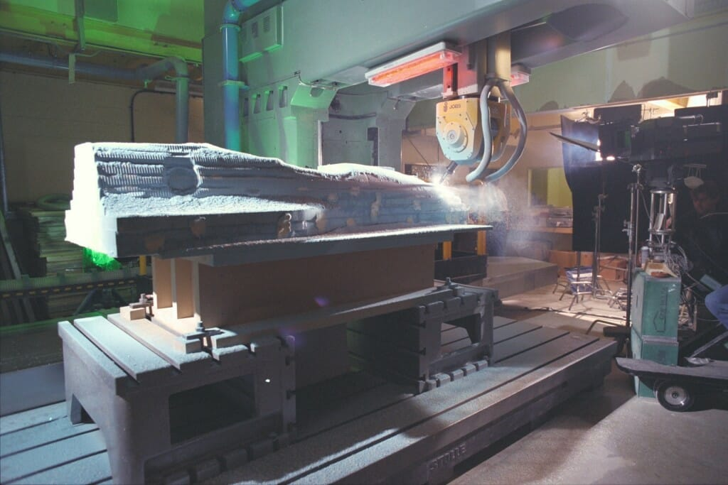 A body mold for an Indy car is shaped by a computer-driven milling machine. The IMAX camera dolly is at right. Photo: Patrick Gariup