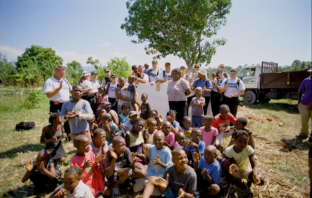 "Canadian Navy personnel with Haitian orphans. Image from the giant screen film ""Rescue"""