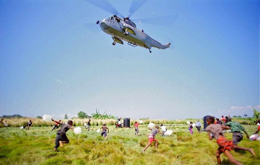 "A Canadian Navy Sea King helicopter makes a water delivery in Haiti. Image from the giant screen film ""Rescue""."